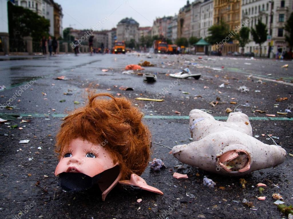 A broken doll head is lying on the floor, street cleaners approaching in the distance — Stock Photo #15741379