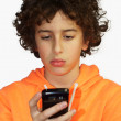 A young boy is looking at his mobile phone - Stock Photo
