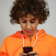 A boy is sending a message on his mobile phone - Stock Photo