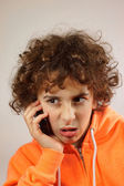A young boy is talking on the phone with a mockery gesture — Stock Photo