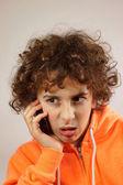 Ein kleiner junge ist mit einer spott-geste telefoniert — Stockfoto