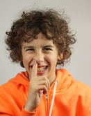 A young boy is picking his nose with a cheeky smile — Stock Photo
