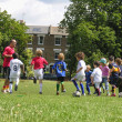 Kids playing football in the park — Stock Photo #23972383