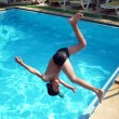 Young boy jumping into pool - Stock Photo