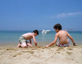 Two boys are playing on the beach — Stock Photo