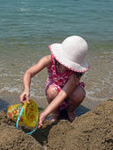 A little girl is playing with sand bucket on the beach — Stock Photo