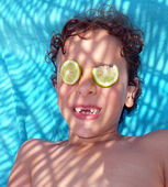 Boy grinning with two lemon slices on his eyes — Stock Photo