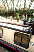 Houseboat on canal with flower pots — Stock Photo