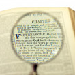 The God word comes bigger under magnifier on a bible page — Stock Photo