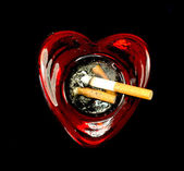 Cigarette butts in a heart shaped ashtray — Stock Photo