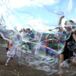 Постер, плакат: Kids enjoy bubble chase