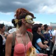 Masked female protester plays tambourine — Stock Photo