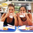 Stock Photo: Women enjoy their fast food