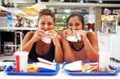 Women enjoy their fast food — Stock Photo