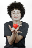 Woman holds heart in her hands — Stock Photo