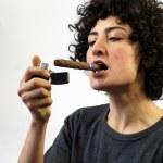 Постер, плакат: Woman lights up a cigar