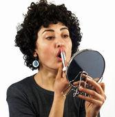 Woman putting on lipstick — Stock Photo