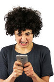 Angry woman looks at her phone — Stock Photo