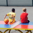 Постер, плакат: Boys sit on a table tennis table in the playground