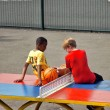 Постер, плакат: Young boys sit on a table tennis table