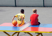 Boys sit on a table tennis table in the playground — Stock Photo