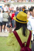 Young woman taking pictures with two cellphone / smartphone — Stock Photo