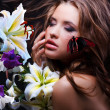 Young beautiful face surrounded by flowers and tropical butterfl — Stock Photo
