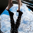 Walking wet barefoot on reflection of the sky in puddle — Stock Photo
