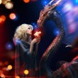 Attractive blonde and big dragon - Stockfoto