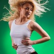 Attractive sport blonde with streamed hair on green — Stock Photo