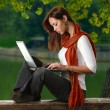 A student girl working with laptop outdoor - Stock Photo