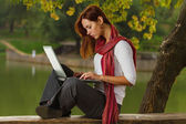 Young girl working with laptop outdoor — Stock Photo