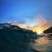 Rough colored ocean wave falling down at sunset time — Stock Photo
