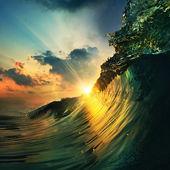 Solnedgång på stranden med skruv ocean wave — Stockfoto