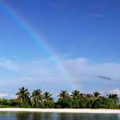 Gün ışığı ile gökkuşağı ufuk ve beyaz kumlu plaj tropikal maldivlere adası — Stok fotoğraf