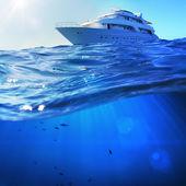 La hermosa luz del sol con vistas al mar safari bote de buceo en mar tropical con azul profundo debajo dividido por la línea de flotación — Foto de Stock