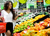 Beautiful young female shopping for fruit and vegetable — Stock Photo