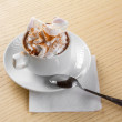 White cup of coffee with cream and caramel sauce on top, with spoon, on the wooden desk — Stock Photo #20427363