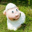 Smile white sheep statue in green grass on daytime — Stock Photo