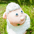 Smile white sheep statue in green grass on daytime — Stock Photo #35416243