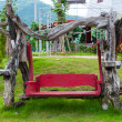 Red empty Wooden Garden Swing bench in the garden or park — Stock Photo