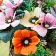 Beautiful colors of artificial plastic small flowers in pot — Stock Photo #35417933