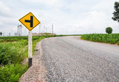 T junction road signpost beside a curve road against cloudy sky — Stock Photo