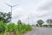 Road way with wind turbines producing power against cloudy sky — Stock Photo