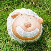 Smile white sheep statue in green grass on daytime — Foto de Stock