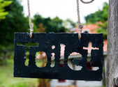Toilet sign on the metal plate hanging in the park or garden — Stock Photo