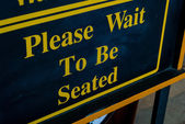 Please Wait To Be Seated Sign — Stock Photo