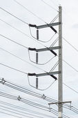 Electricity voltage post with wire on the very cloudy sky — Stockfoto