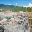 Huge construction site for dam with cranes in mountain area — Stock Photo