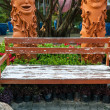 Old wooden bench in the garden with strange decorations. — Stock Photo